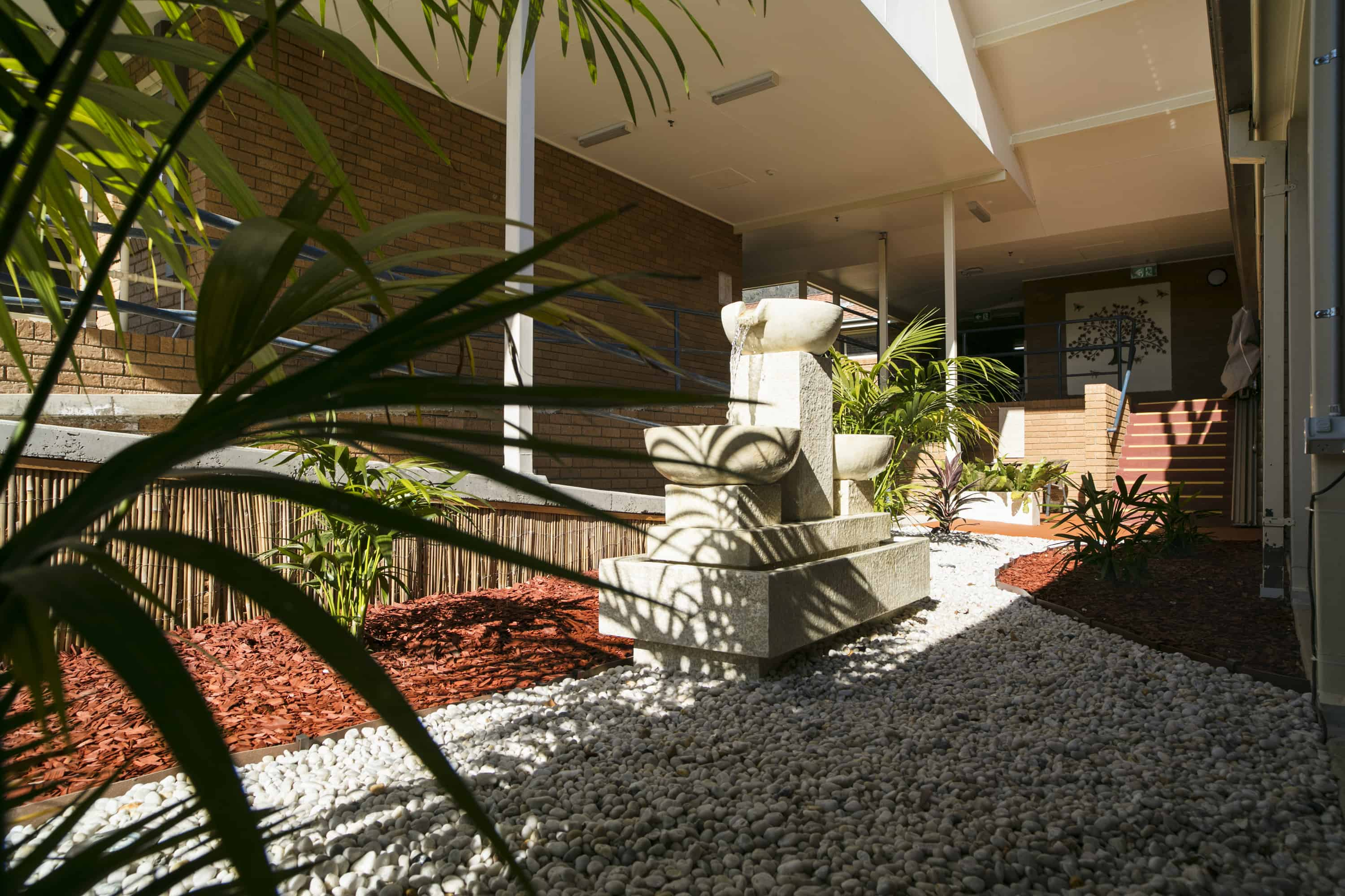 Front entrance of Whiddon Laurieton's residential aged care home, fitted with a water fountain and lush plants.
