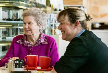 A Whiddon carer and resident from Whiddon Kelso enjoying coffee together at a social outing.