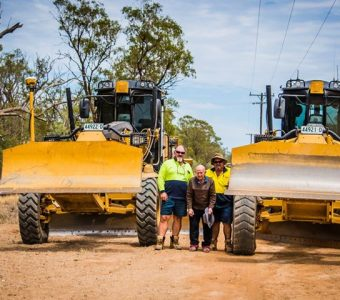 Whiddon Narrabri resident, Ron, smiling with two grader operators as part of Whiddon's Best Week initiative.